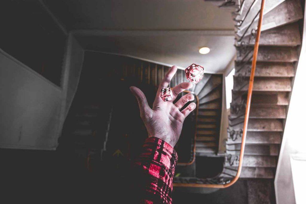 De hand gooit de dobbelstenen