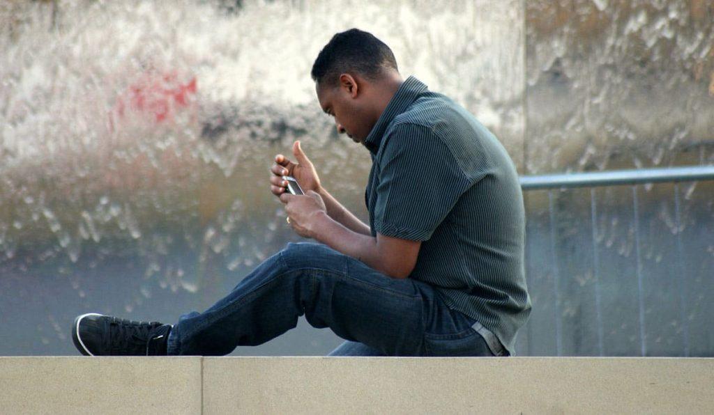 De man kijkt naar het telefoonscherm