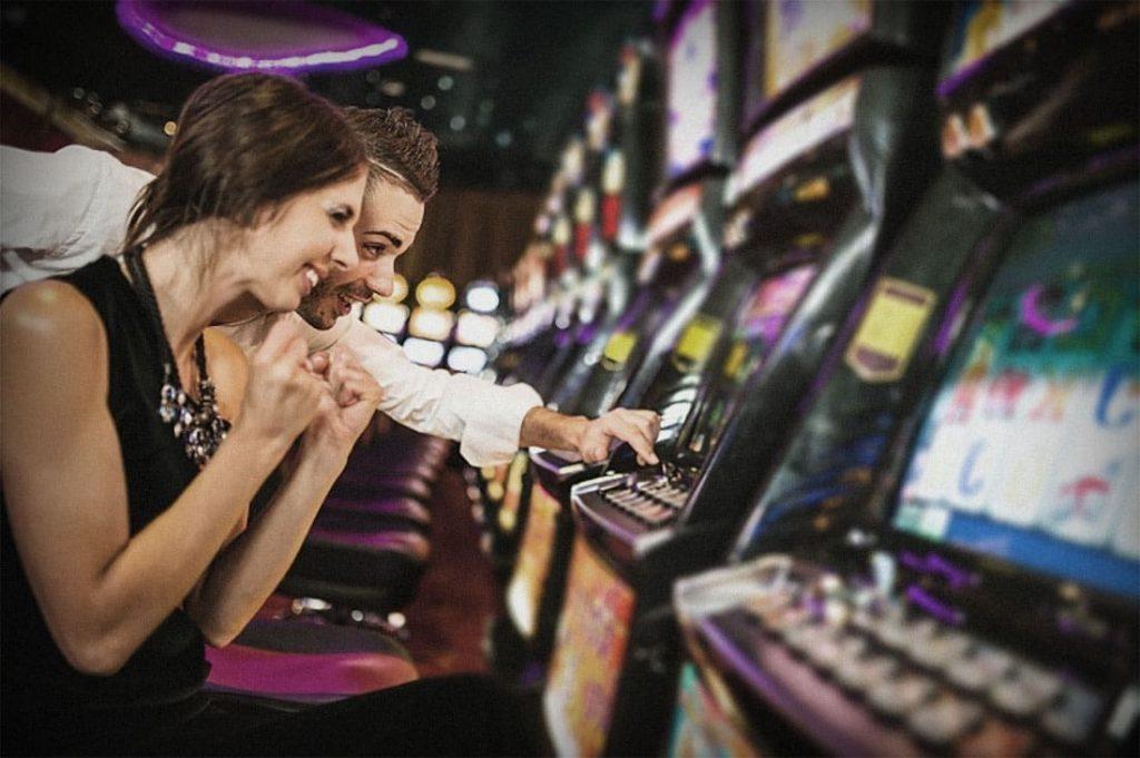 Een jongen en een meisje spelen op een gokautomaat